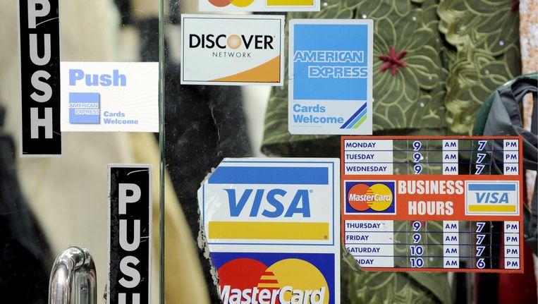 Een deur van een restaurant met creditcardreclame. Beeld afp