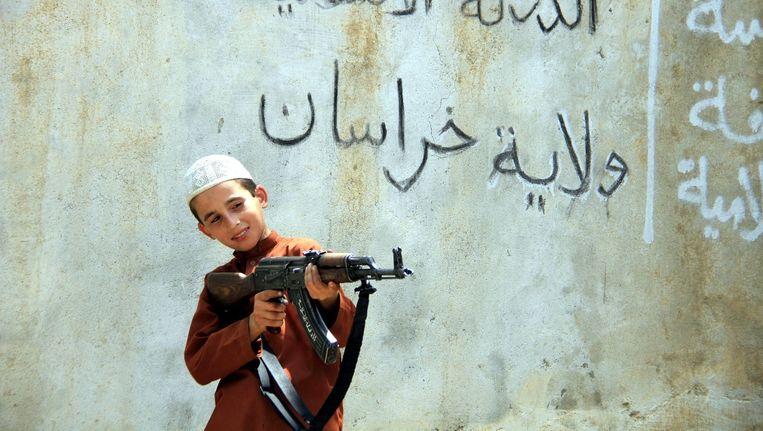 Een foto, beschikbaar gesteld op 1 augustus 2015, van een jongetje met een AK-47 in Afghanistan. Volgens EPA hoort het jongetje bij een IS-militie. Beeld epa