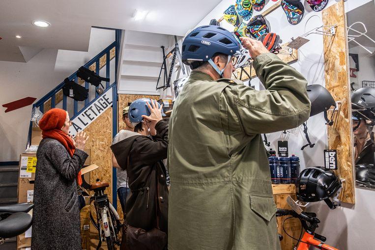 Onwennig passen Parijzenaars een fietshelm, maar ook het fietsen zelf is nieuw voor ze.  Beeld Joris Van Gennip