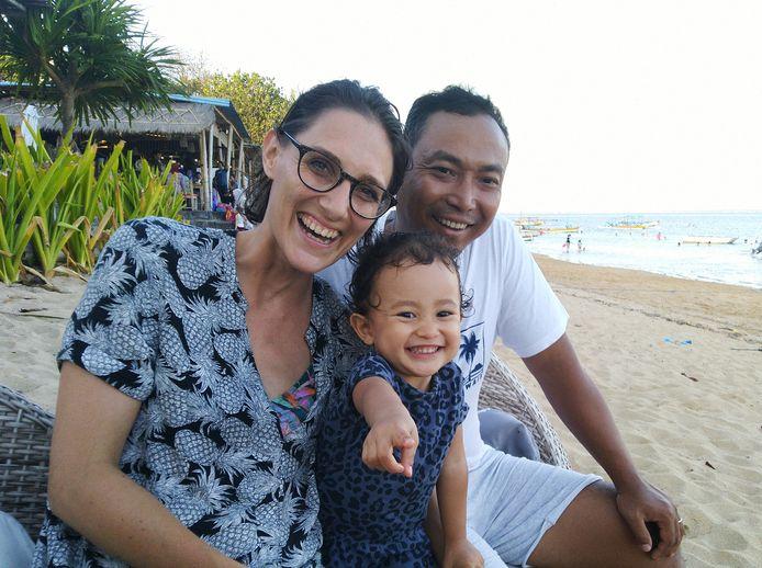 Marieke Nijland, haar man Putu Ben en dochtertje Nina op het strand van Sanur Bali. ,,Alle drukte gestopt door virus.''