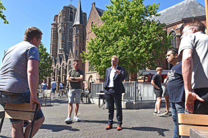 Burgemeester Buijs gaat in discussie met horeca-ondernemers op de Oosterhoutse Markt.