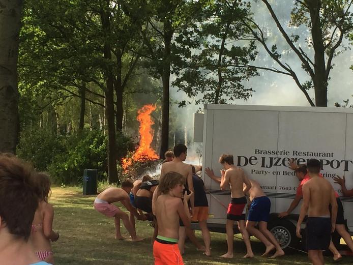 De aanwezige jeugd duwt een aanhanger weg bij het vuur