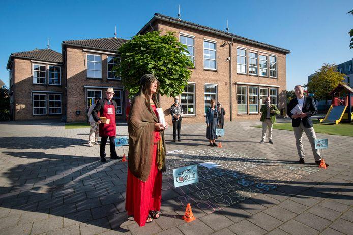 De pastores en de leden van de groep Vrij-Fridus bij de honderd vakken op het schoolplein. Voor Janine Kallen als Maria Magdalena, links (met hoed en schort) pastoor Karel Donders.