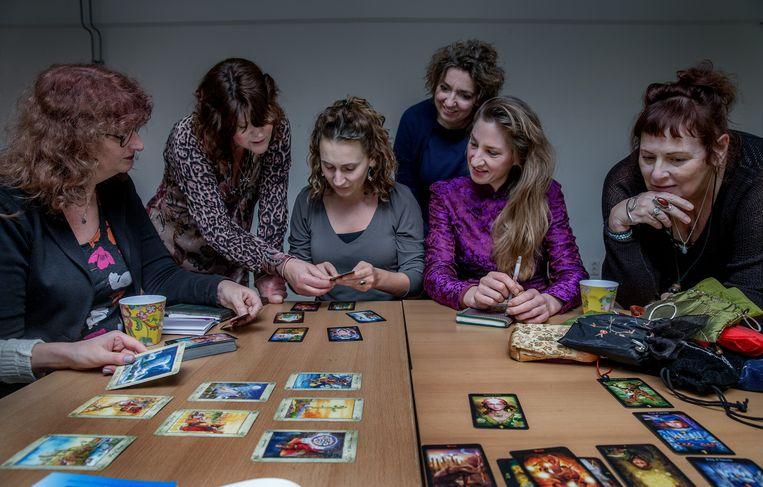 Docent Monique van de Raapkamp (staand links) kijkt toe bij een cursus tarotkaarten leggen in Amsterdam. Beeld Jean-Pierre Jans