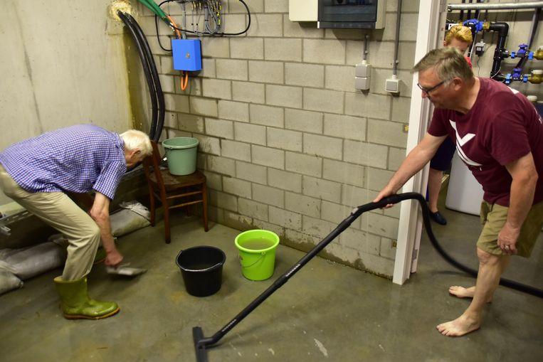 Bewoners van residentie Dorpzicht proberen het water weg te krijgen uit de kelder van hun flatgebouw.