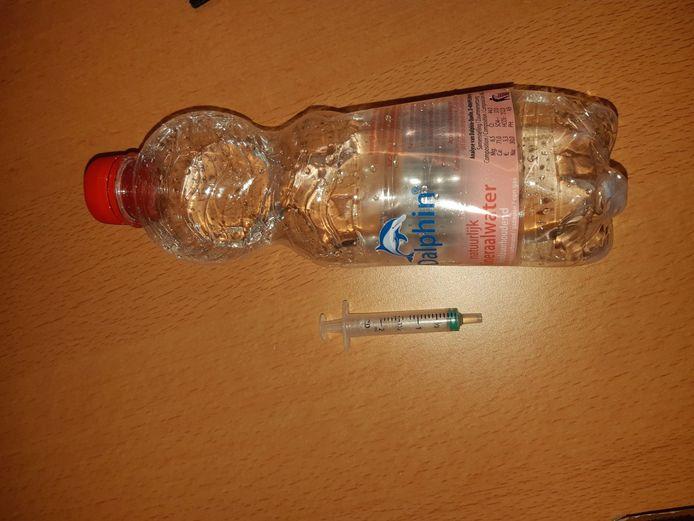 Het flesje met daarin vermoedelijk GHB en het spuitje om de dosering mee af te meten.