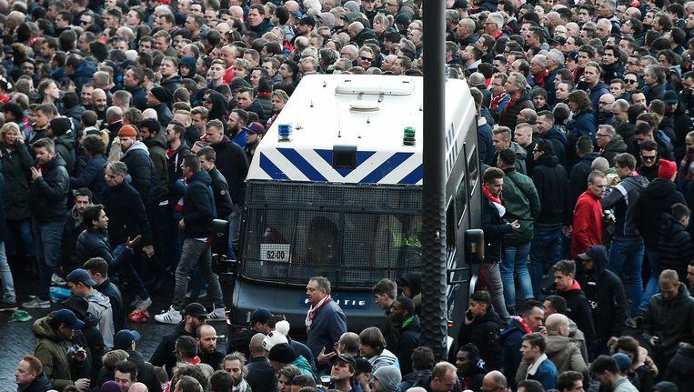 Supporters rond een busje van de politie voor de eerste wedstrijd tussen Ajax en Juventus. Beeld AFP