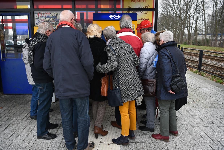 Een groep reizigers bestudeert een automaat van de NS. Beeld Marcel van den Bergh