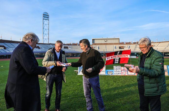 Ronald Ockhuysen reikt het eerste exemplaar van de scheurkalender van FC Amsterdam uit aan (oud)voetbalspelers  (van links naar rechts) Rob Bianchi, Heini Otto en Jan Jongbloed in het Olympisch Stadion.