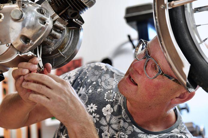 Jan van den Berg sleutelt aan een Puch waar hij een elektromotor in heeft gezet.
