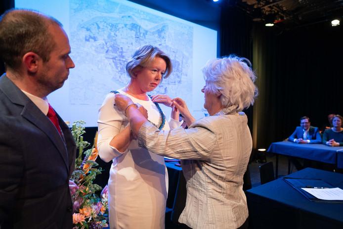 Patricia Hoytink-Roubos krijgt de burgemeestersketen omgehangen door waarnemend raadsvoorzitter Hannie van Brakel.