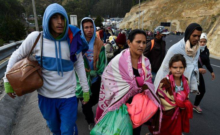 Venezolanen lopen over de Pan-American Highway door Ecuador, op weg naar Peru. Beeld AFP