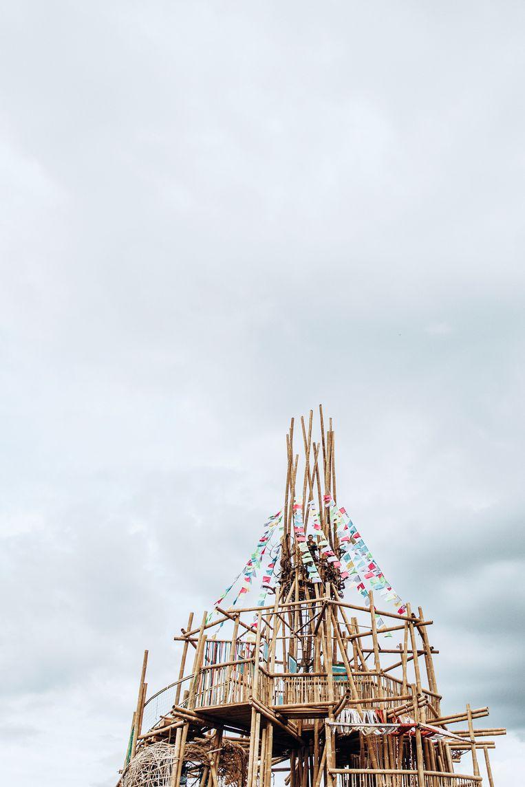 Prachtig is de Toren van Babel, opgetrokken uit bamboe en hout, die verrees op 'den Dam', een wijk in het noorden. Op 9 april 2020 is de toren in de as gelegd door iemand met zware psychische problemen. Beeld Sofie Gheysens