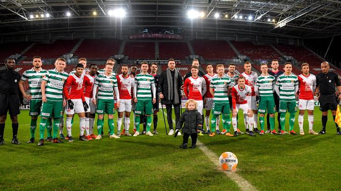 De teams van Jong FC Utrecht en GA Eagles voor de wedstrijd met Leon de Kogel (midden).