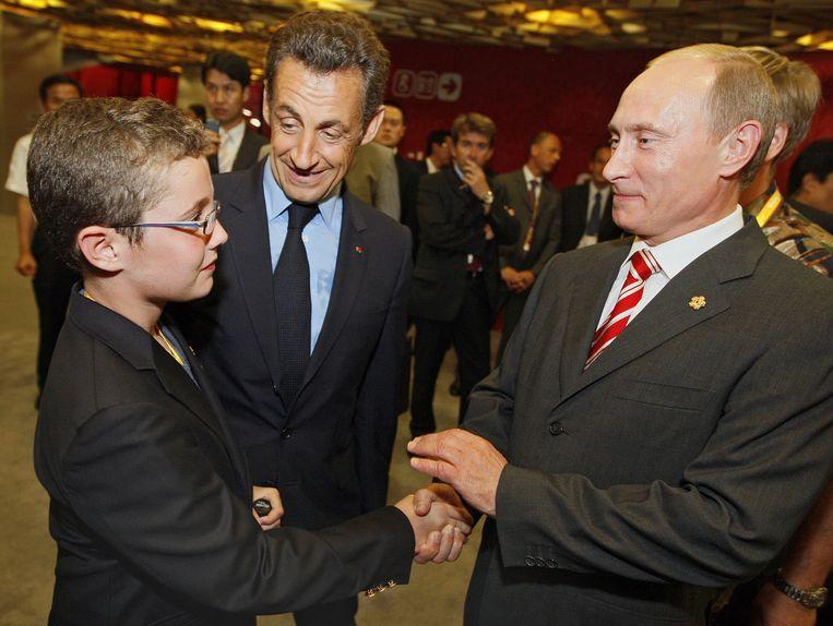 De Franse president Nicolas Sarkozy stelt zijn zoon Louis voor aan de Russische premier Vladimir Poetin (rechts). De foto is in 2008 genomen tijdens de openingsceremonie van de Olympische Spelen in Peking. Beeld afp