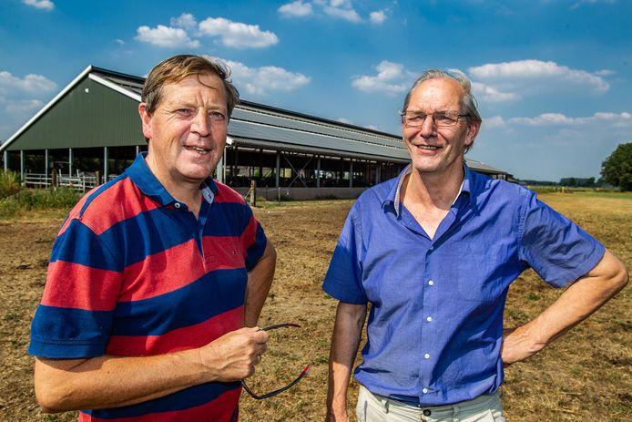 Willem van Stockum  (links) en Dik Matthes bij de zonnecollectoren op een stal in Warnsveld.