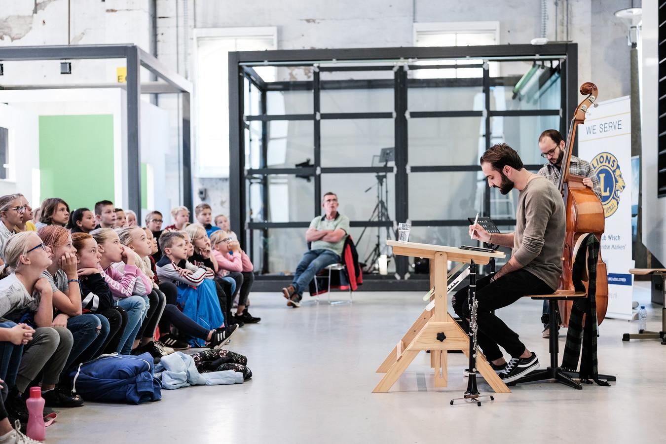 Haidar Habash tijdens een voorstelling voor scholieren, met zijn muzikale begeleiders Bariş Ofluoğlu en Ghaeth Almaghoot.