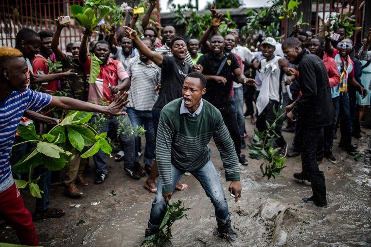 Congolezen protesteren bij een stembureau in Kinshasa, waar de voorzitter van de kiescommissie op dat moment arriveert. Beeld AFP/Luis Tato
