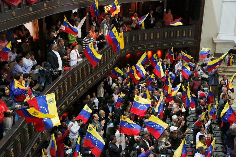 Leden van de Grondwetgevende Vergadering zwaaien met Venezolaanse vlaggetjes.