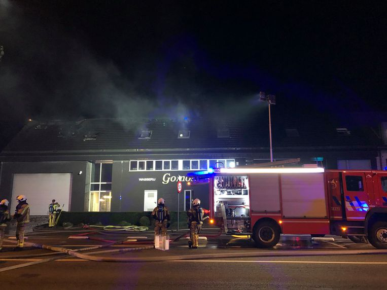 De brandweer blust de dakbrand in het wassalon aan de Leugenberg in Ekeren.