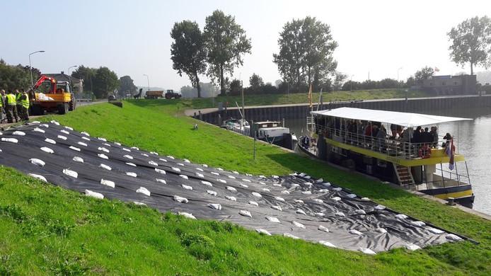 Genodigden kijken vanaf de boot toe hoe militairen de Grebbedijk bij Wageningen versterken.