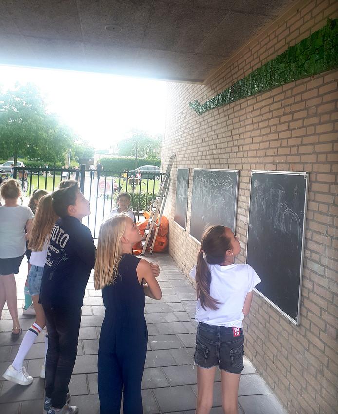 Leerlingen bekijken kunstwerk na onthulling bij 10-jarig jubileum van basisschool De Wending. Foto Alfred de Bruin