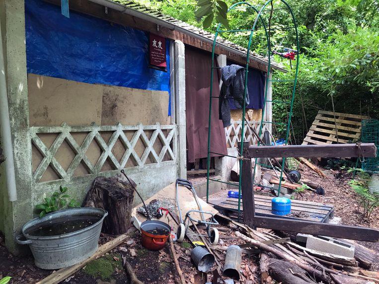 Buiten de hut ligt het vol met rommel.