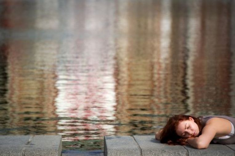 Een vrouw geniet volop van het zomerse weer op het Museumplein in Amsterdam. ANP Beeld
