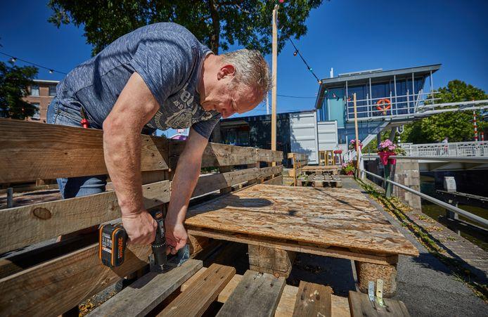 Eigenaar Peter Bender van cafe De Ooievaar in Delfshaven moet zijn extra Corona-terras aan het water weer afbreken.