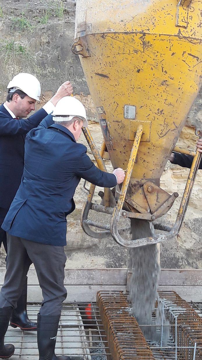 Wethouder Berend de Vries en Jark Schepens (Van de Ven, op de rug) storten 'een mop beton' voor de keldervloer van het Tilburgs Arsenaal.