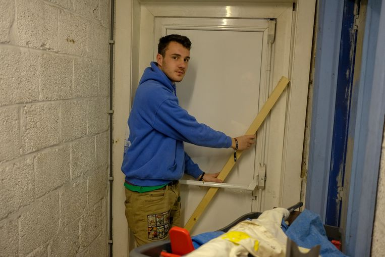 Onder meer met een houten stok probeert de leiding de branddeur beter te beveiligen.