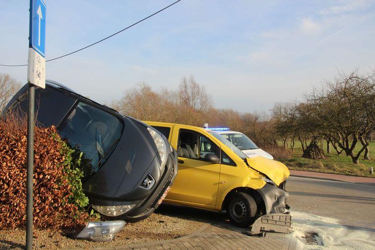 De Peugeot belandde in de haag en op het dak van de aanrijdende bestelwagen.