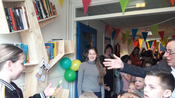 Wethouder Jan Brekelmans bekijkt het nieuwe kinderzwerfboekenstation met de leerlingen van basisschool De Start in De Moer.