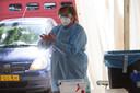 De auto rijdt de tent binnen. Twee medewerkers staan klaar. De handen worden gedesinfecteerd voordat de handschoenen aan gaan.