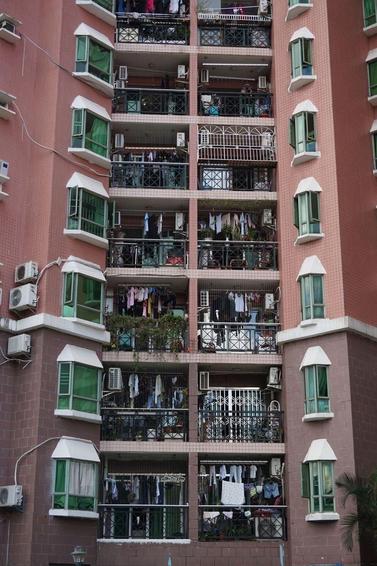 Waslijnen op balkonnetjes sieren het kleurrijke huizencomplex aan de Guihua Road in Shenzhen.  Beeld null