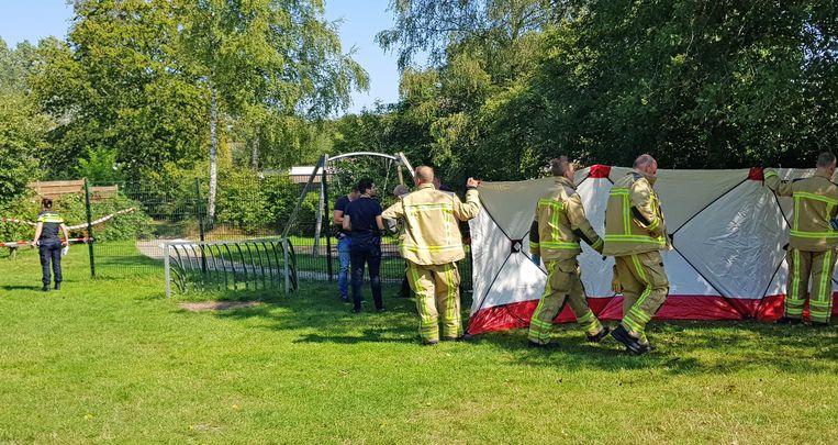 Hulpverleners plaatsen een scherm in een speeltuin waar een man om het leven is gekomen.  Beeld ANP