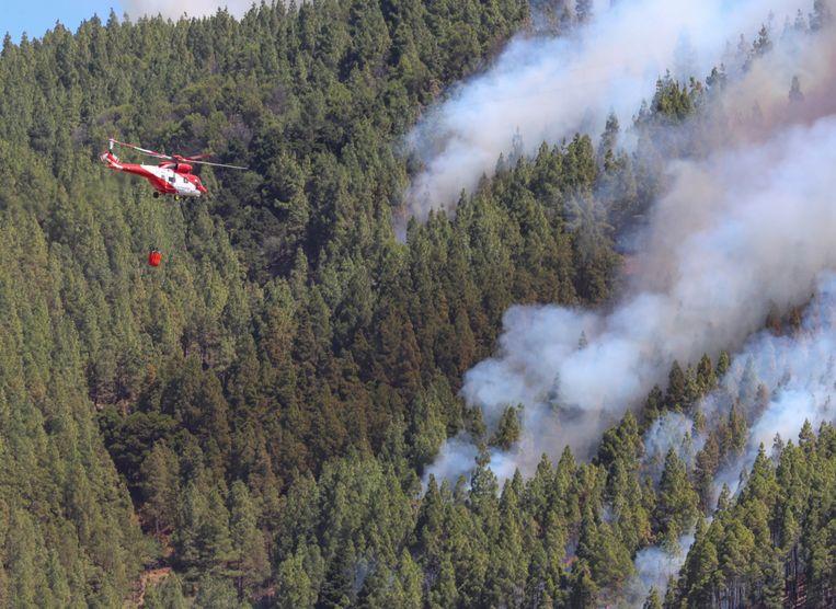 Een helikopter probeert het vuur te blussen in Artenara.