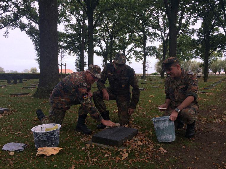 Luitenant-kolonel Peter Weyers en twee reservisten van de Bundeswehr geven een graftegel een opfrisbeurt.