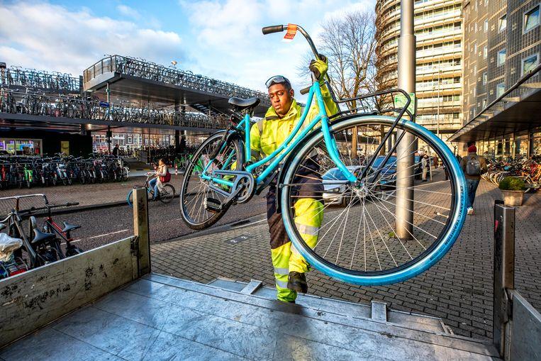 Een fietshandhaver verwijdert een Swapfiets bij het Centraal Station in Amsterdam. Beeld null