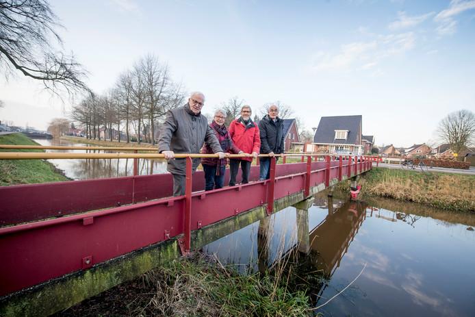 Rien de Greef, Lies te Kiefte en Hans Vlietstra van de Historische Werkgroep Lemelerveld (v.l.n.r.) op het voetgangersbrugje met ontwerper Wim Spijkerman.
