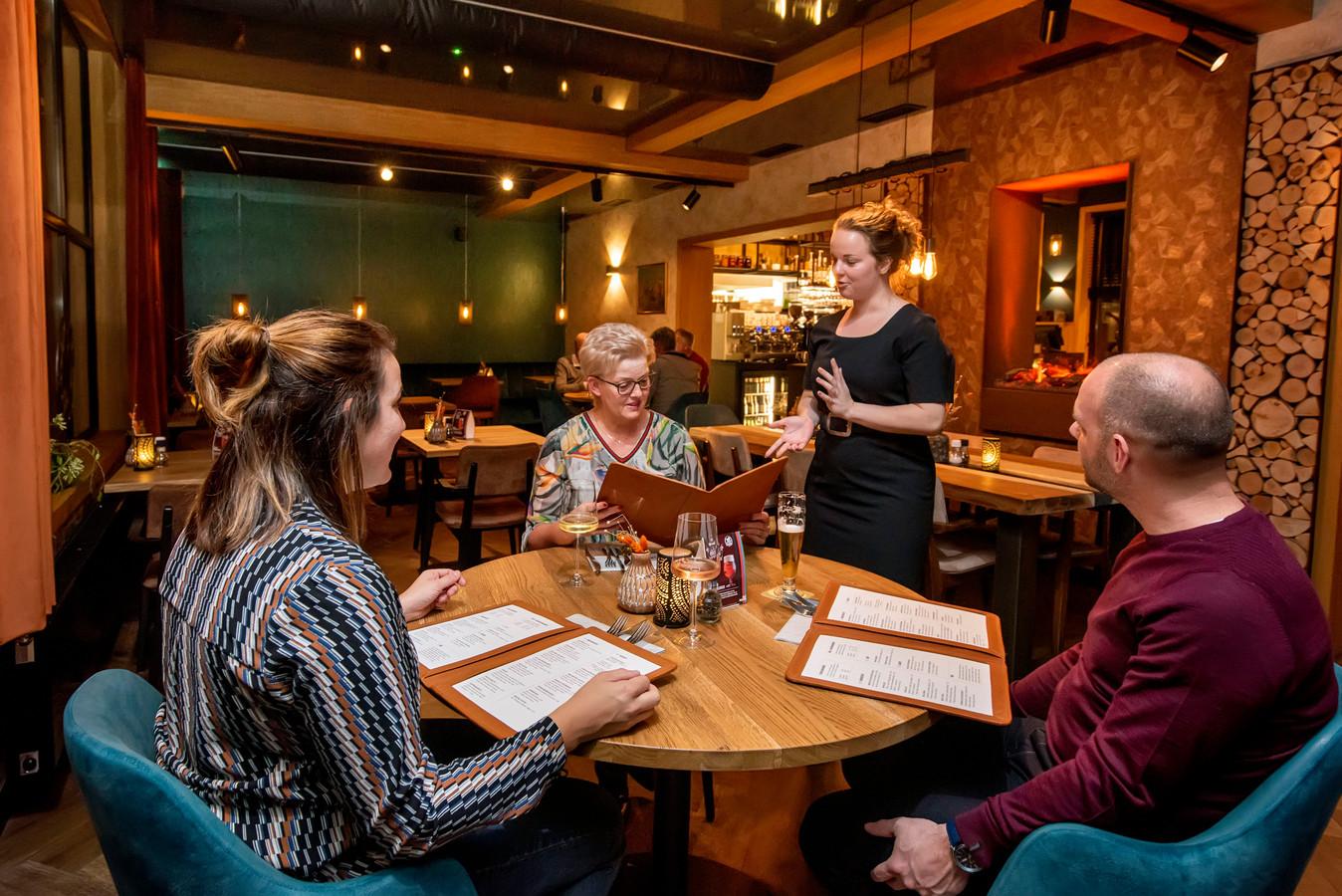 Gastvrouw Laura Pijpers geeft uitleg over de menukaart van De Huyskamer in Gilze.