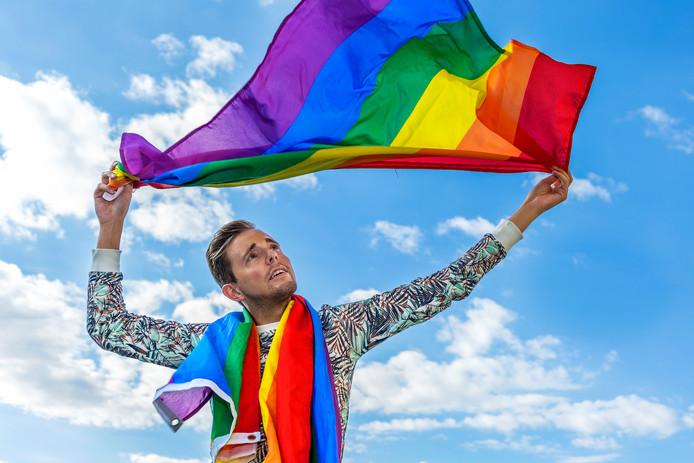 Simon Timmerman, voorzitter van COC Midden-Nederland, met de regenboogvlag. Die wordt vandaag vanwege Coming Out Dag op veel gemeentehuizen in top gehesen.