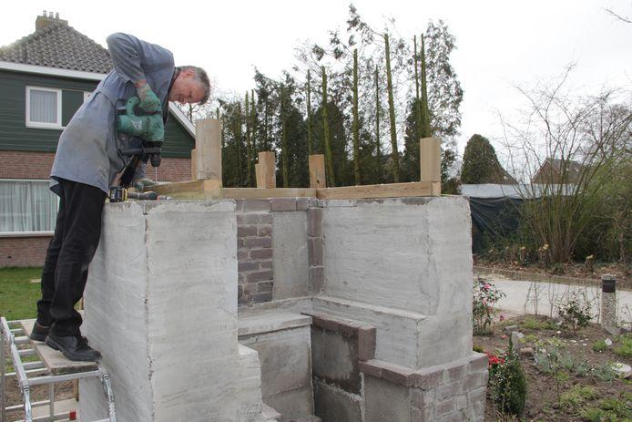 Pastoor Rudo Franken bouwt zelf een kapelletje in de tuin van de pastorie in Millingen.