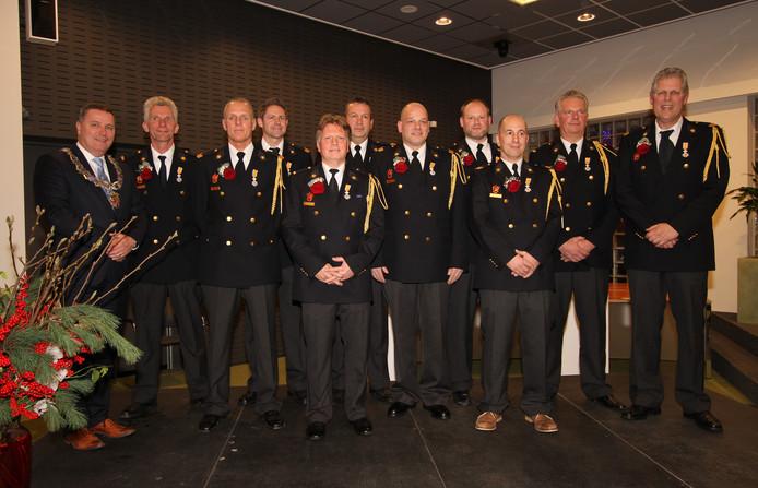 De tien gedecoreerde brandweermannen.