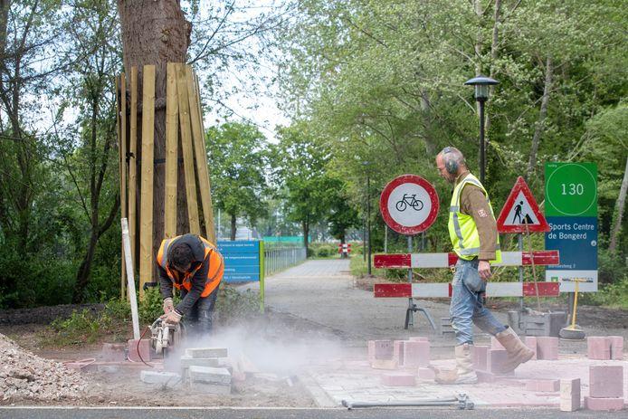 Wegwerkers leggen de laatste hand aan een nieuwe oversteek voor fietsers over de Nijenoord Allee tussen de Hoevestein en de zij-ingang van universitair sportpark De Bongerd.