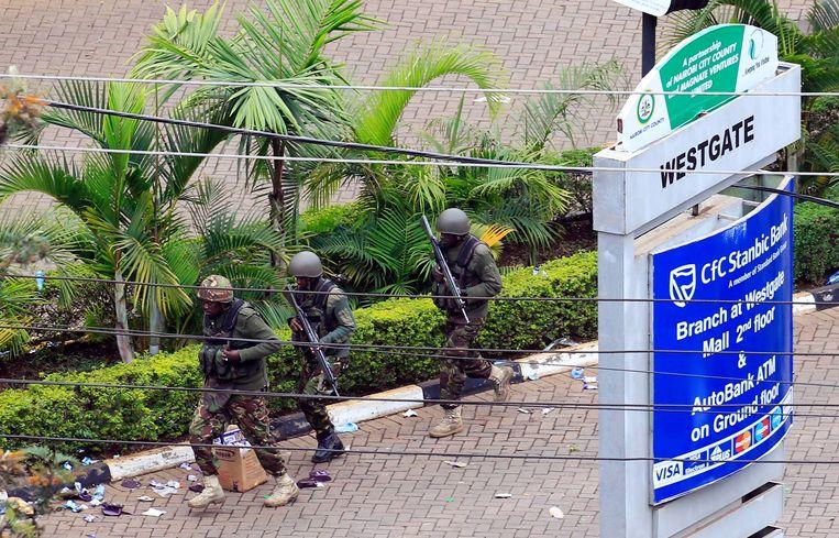 Keniaanse militairen proberen het winkelcentrum Westgate binnen te dringen, waar militanten van al-Shabaab zich in september vorig jaar schuil hielden. Beeld REUTERS