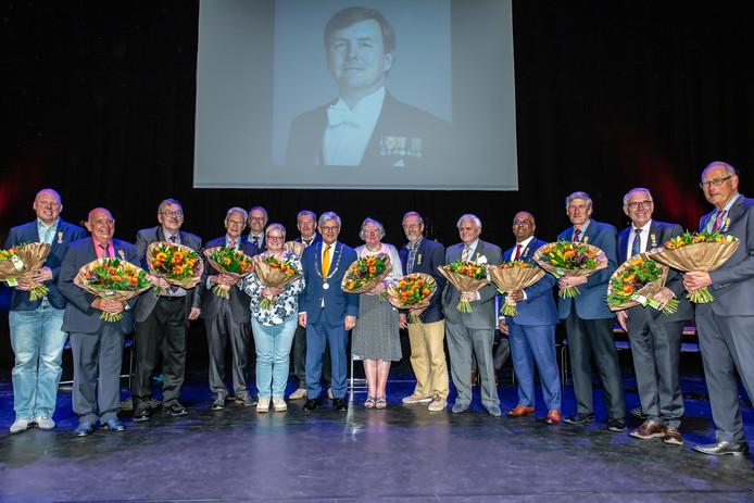 Burgemeester Charlie Aptroot tussen de ontvangers van de lintjes op het podium van het Stadstheater.