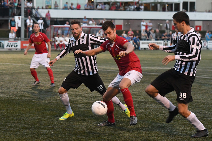 JVC'er Thomas Schilders tussen Achilles-spelers Coen Gortemaker en Levan Jordania in.