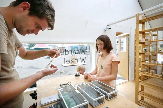 Kunstenaar Pavel van Houten bekijkt een hoopje tabak dat Zus en haar broertje Ties hebben meegebracht.