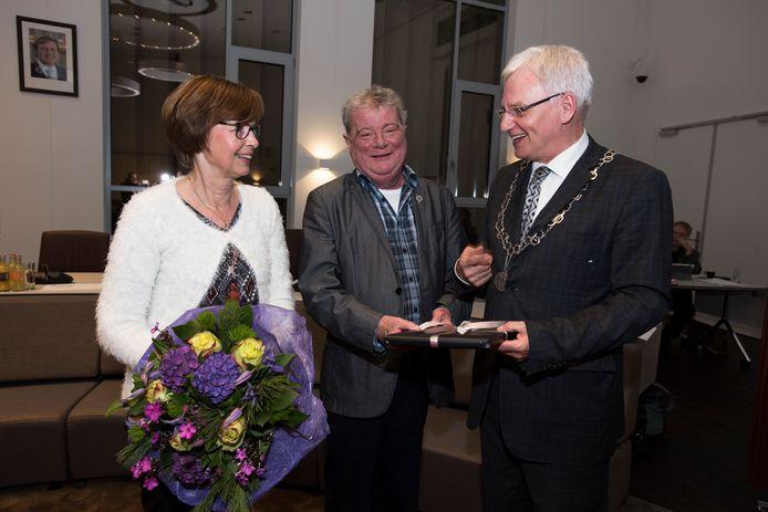 Jan in 't Groen krijgt van de burgemeester de zilveren erespeld, links zijn echtgenote Marij.